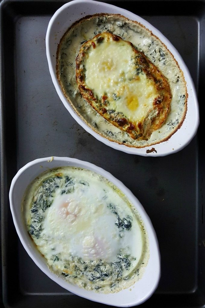 Spinach Baked Eggs may sound plain, but they're definitely are anything but that!  Eggs are baked in delicious and flavorful creamed spinach and topped with Parmesan cheese. Serve with garlic toast for a special brunch or #meatfree dinner.