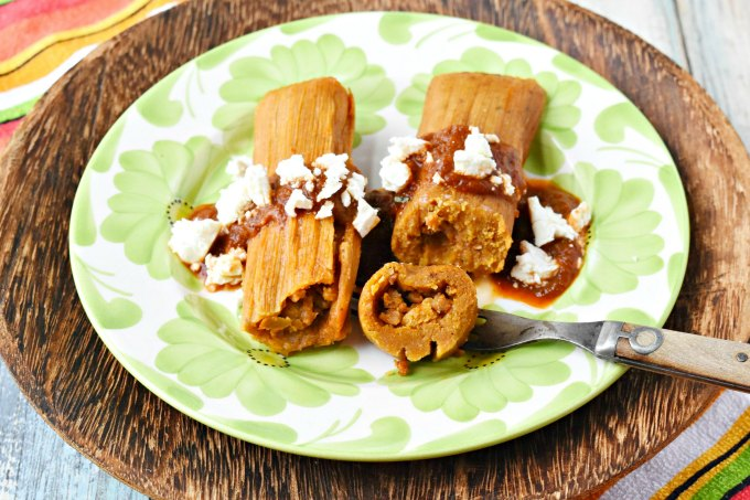 Savory pumpkin masa dough is filled with spicy pork chorizo.  Pumpkin Chorizo Tamales with Pumpkin Mole is a flavor-plosion in your mouth!  If that's not enough, they're topped with rich pumpkin mole and creamy queso blanco.  #PumpkinWeek