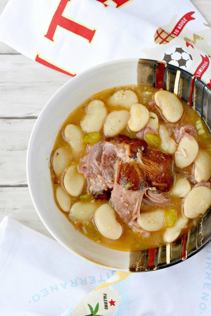 Braising the hickory smoked turkey legs in chicken broth make for a rich broth used to cook butter beans. Smoked Turkey Legs with Butter beans in Tomato Pesto Broth has a smoky, tomato broth and large butter beans. It's a rich meal that will warm you up on the coldest nights. #fricks, #smokedmeats #itsfrickingood