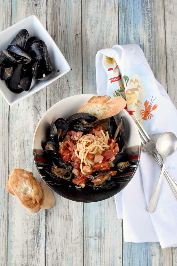 Tender mussels swim in a white wine tomato broth with garlic, shallots, proscuitto, and herbs.  Perfect for date night or a dinner party, Spicy Mussels Provençal are similar to a bouillabaisse style dish with less broth and a little more spice.  Oh, and pasta.