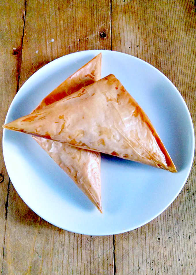 Delicious pumpkin is sauteed with onions, garlic, carrot, and chickpeas and baked in phyllo dough triangles to make these Pan Roasted Pumpkin and Chickpea Samosas.