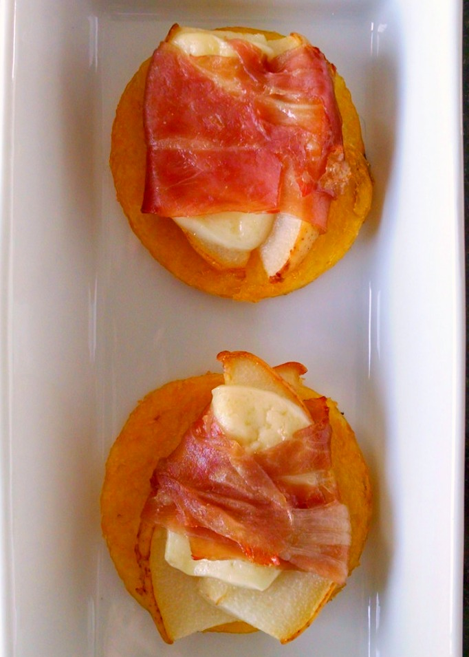 Pear, Proscuitto, Polenta Bites | A Kitchen Hoor's Adventures | Polenta rounds are baked until crisp then topped with pears wrapped in prosciutto and baked until the prosciutto is crisp