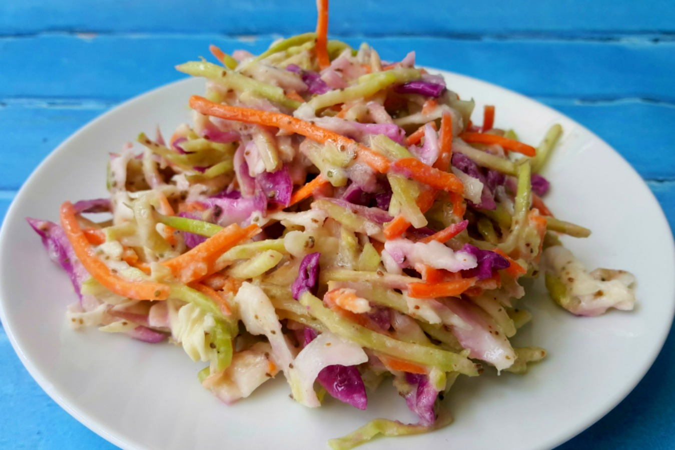 The hubs says this Kicked Up Coleslaw is the perfect recipe! It has the perfect amount of spice, sweet, and sour with the delicious crunch of broccoli slaw.