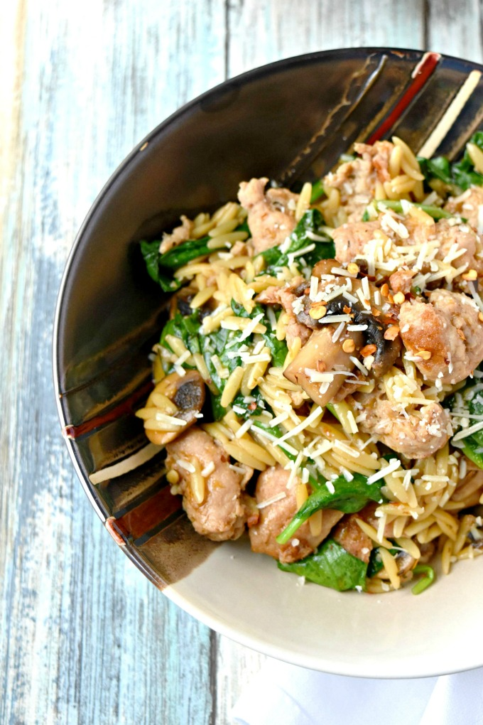 One Pot Italian Sausage Orzo with Spinach and mushrooms garnished with Parmesan cheese and crushed red peppers.