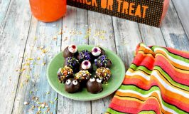 You need to make candy corn moonshine. It tastes out of this world! And it turns delicious cookies into these fun Candy Corn Moonshine Truffles made with vanilla cookies. #HalloweenTreatsWeek