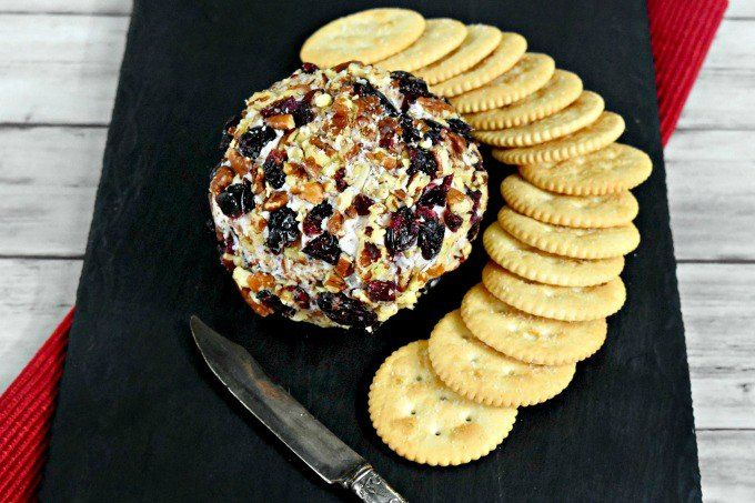 Cranberry Cheese Ball has a simple name, but not simple flavors. Dried cranberries, rosemary, Menorca Spanish cheese, and cream cheese all come together for a delicious cheese ball rolled in roasted pecans and dried cranberries. It's the perfect appetizer for the holidays.