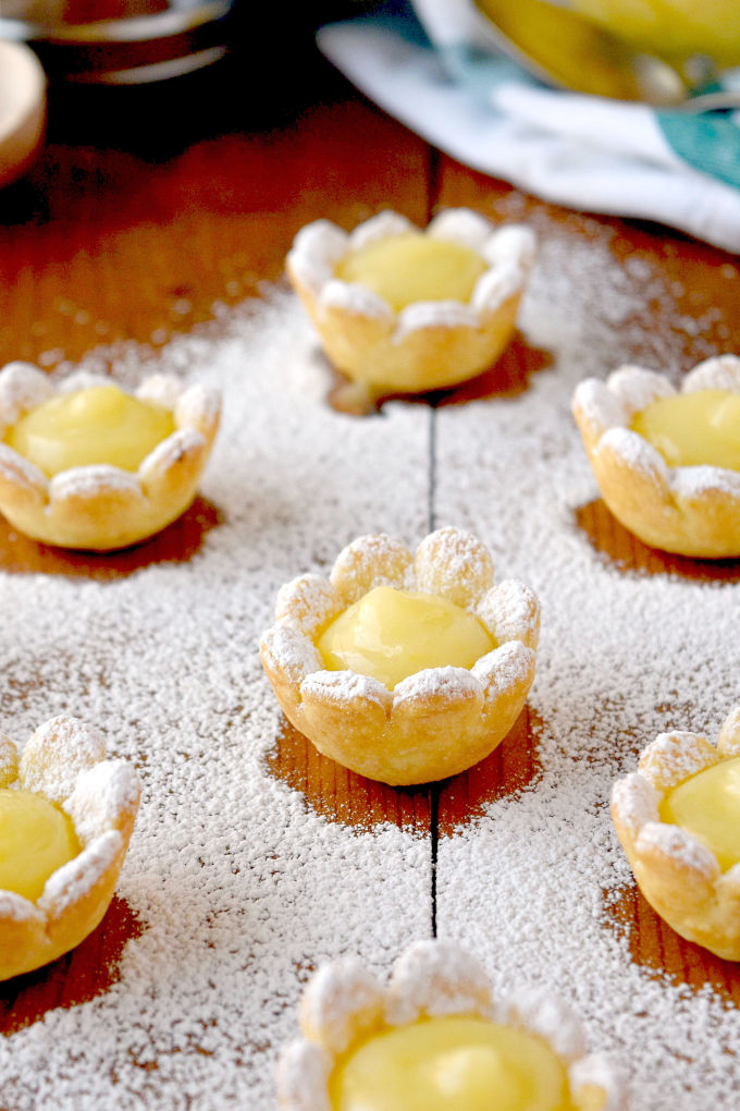 These dainty little flowers are super easy to make. Even the curd is easy because it's made in the microwave! Lemon Daisy Tartlets are super cute and packed with sweet tart flavor of fresh lemon curd. They're perfect for spring time menus! #SpringSweetsWeek