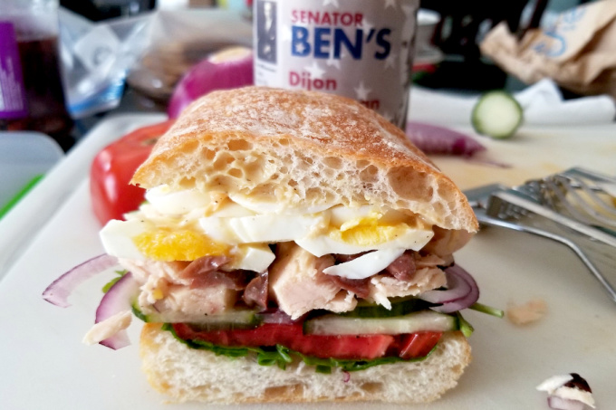 """A delicious farmer's market find tops this Dijon Pan Bangat sandwich. It's rich, delicious, and packed with flavor. Perfect for picnics, pan bagnat need time to """"marinate"""" before eating. #FarmersMarketWeek"""