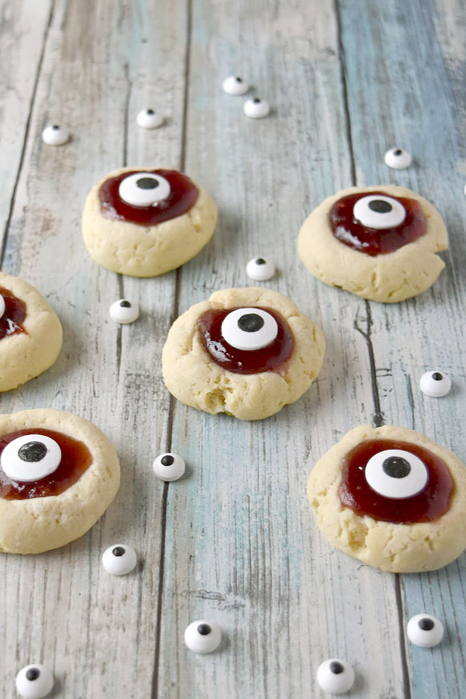Turn a simple and easy thumbprint cookie into Eyeball Thumbprint Cookies! Filled with cherry jam and topped with large candy eyes for a fun Halloween treat. #HalloweenTreatsWeek