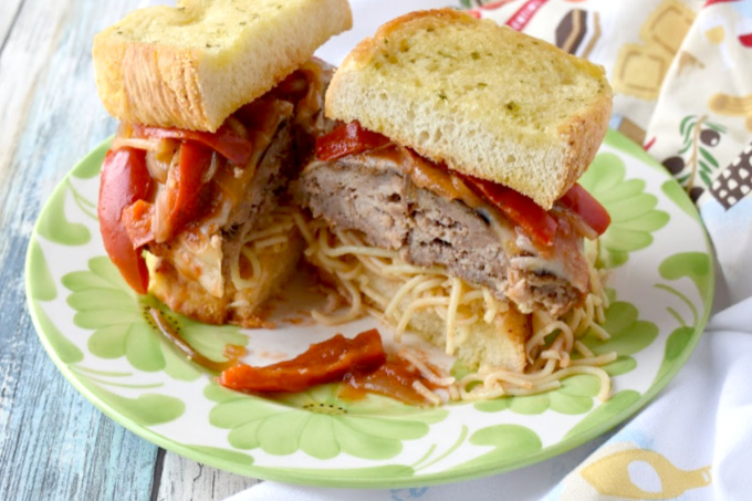 Italian sausage and ground pork come together in this Italian Sausage Parmesan Burger. It's packed with Italian flavors, topped with cheese, and sits on top of spaghetti and Texas toast garlic bread. #BurgerMonth
