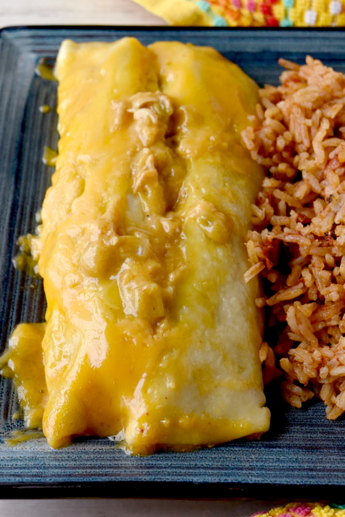 Easy Green Chile Chicken Enchiladas are super scrumptious, super easy, and almost everything comes from your pantry.  The chicken can either be canned or leftover roasted chicken.  Either way these are DE-licious. #OurFamilyTable