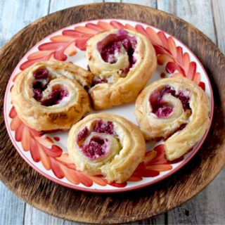 Raspberry Danish Pinwheels come together in minutes and taste simply delicious! The delicious puff pastry, fresh raspberries, and cream cheese filling makes these irresistible. #BerryWeek