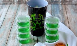 Radioactive Jell-O Shots are a simple gin and tonic with lime Jell-O.  The tonic water makes them glow under a black light which makes them even more fun to eat! #HalloweenTreatsWeek