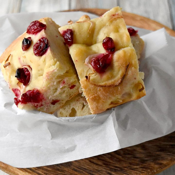 Cranberry Focaccia is super easy and mostly hands off.  It's topped with roasted cranberries and shallots and perfect dipped in olive. #CranberryWeek