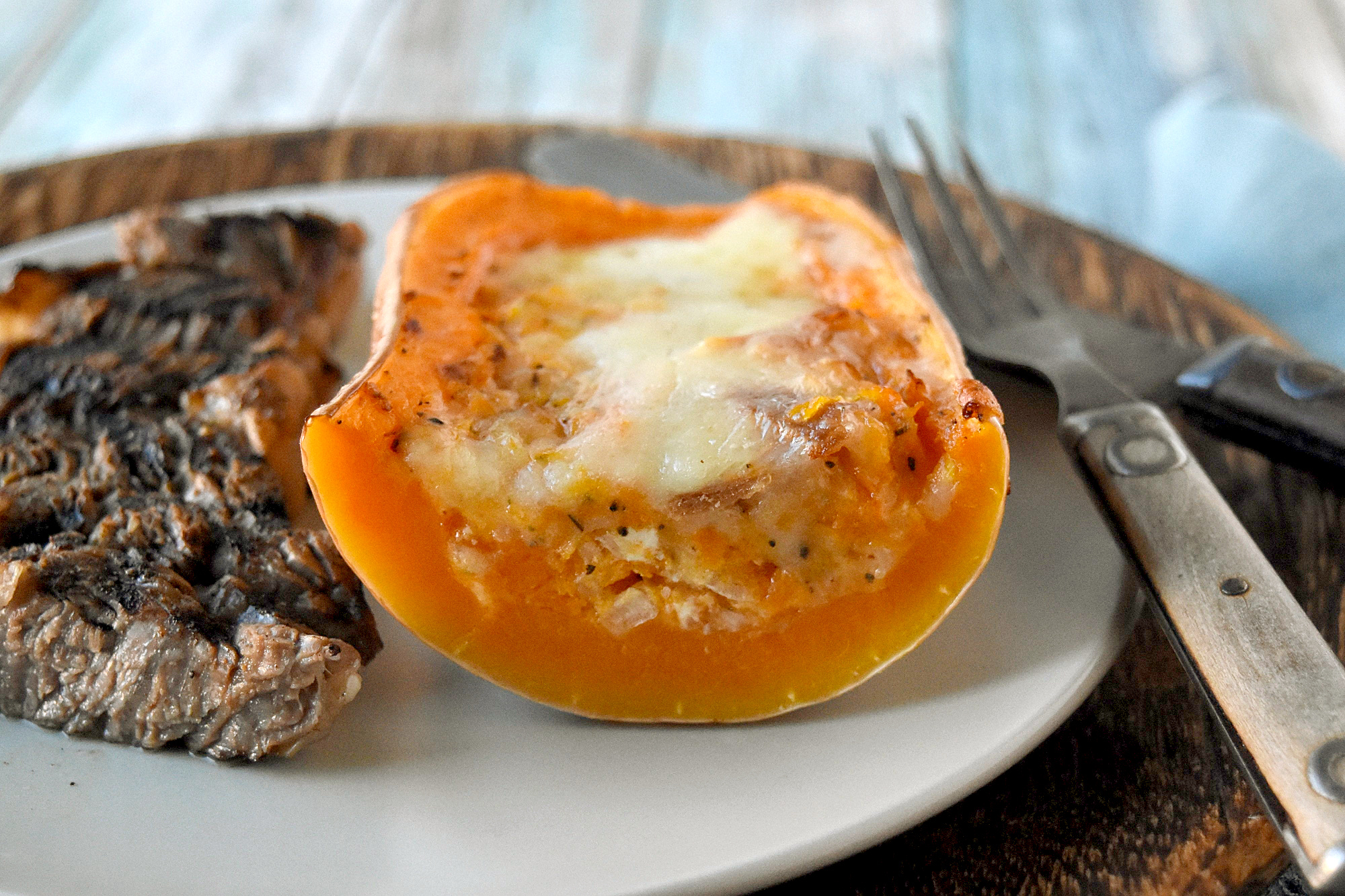 Twice Baked Butternut Squash is a twist on the twice baked potato. The sweet squash is combined with prosciutto, goat cheese, and shallots then topped with Gruyere cheese for a truly scrumptious side dish. #HolidaySideDishes
