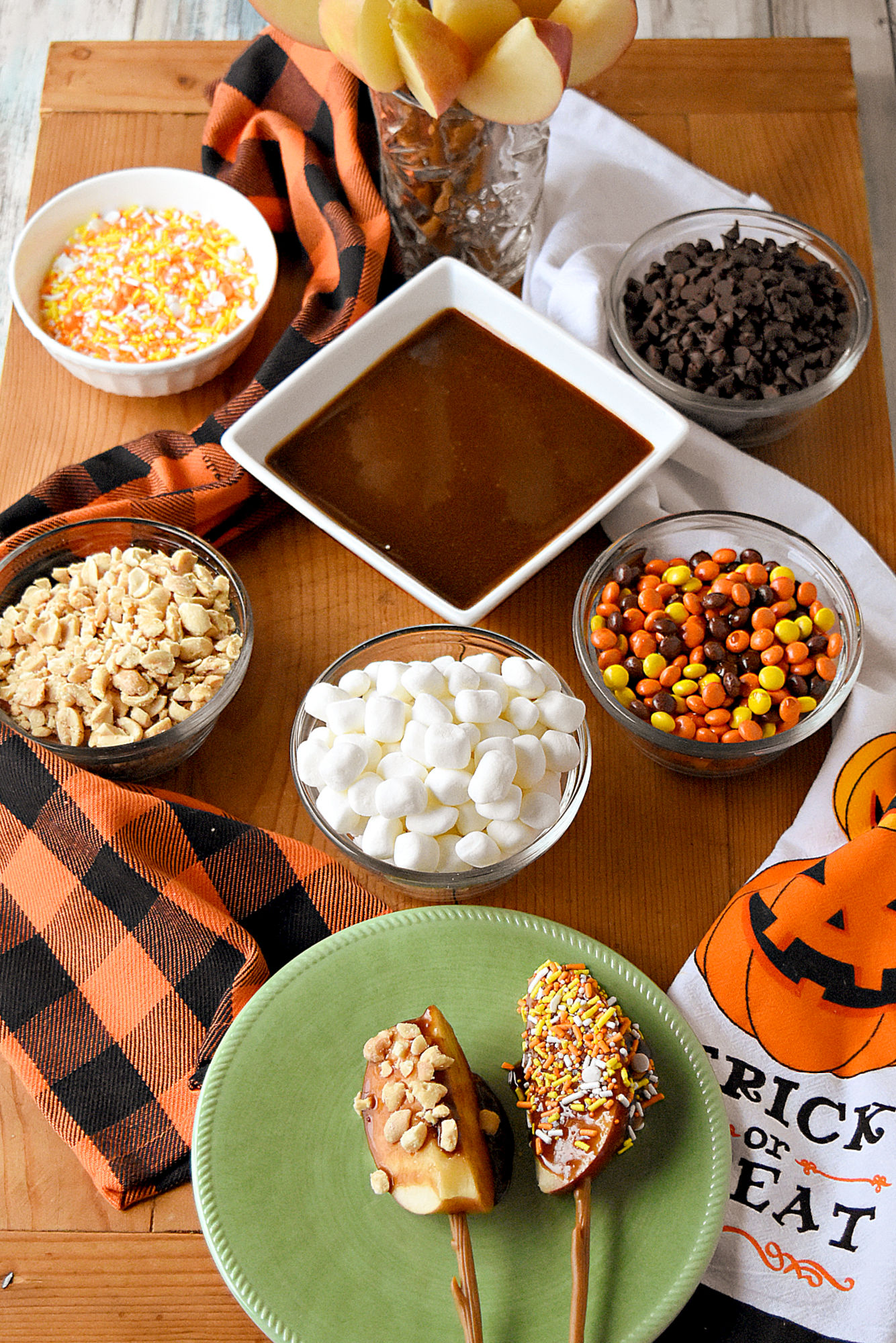Caramel Apple Board is packed with fun toppings and a delicious peanut butter caramel. Made with brown sugar, the caramel sauce is simple to make and tastes delicious. #HalloweenTreatsWeek